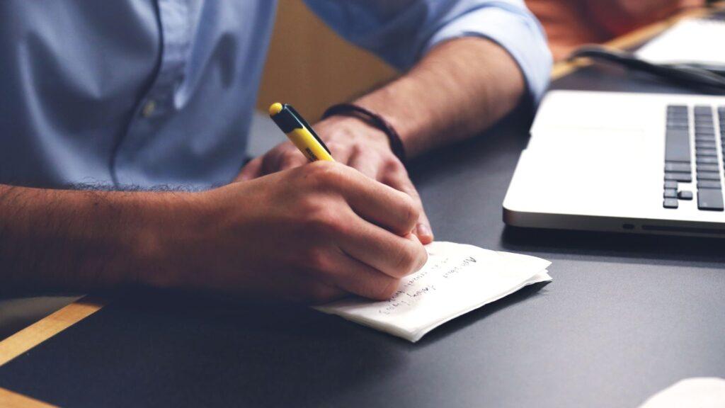 ノートににメモをとる男性