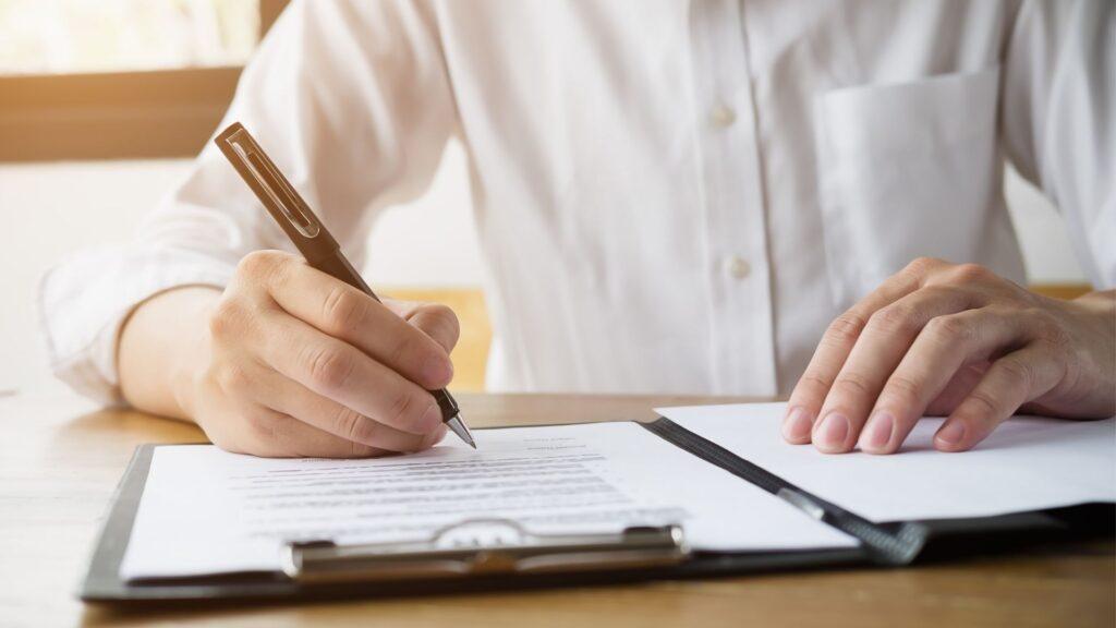 書類にサインを書いている人